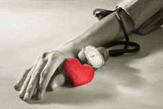 Καρδιά με το βραχίονα γυναικών που ελέγχει τη πίεση του αίματος στοκ φωτογραφία με δικαίωμα ελεύθερης χρήσης