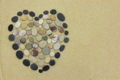 Καρδιά πετρών παραλιών χαλικιών στη χρυσή άμμο Στοκ Εικόνα