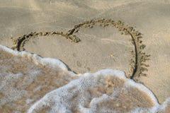 Καρδιά που επισύρεται την προσοχή στην άμμο παραλιών Στοκ Φωτογραφία