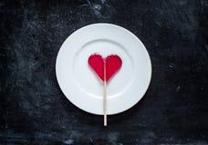 Καρδιά που διαμορφώνεται κόκκινη lollipop στο πιάτο - ημέρα βαλεντίνων Στοκ εικόνες με δικαίωμα ελεύθερης χρήσης
