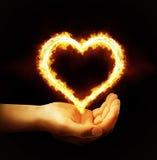 Καρδιά πυρκαγιάς εκμετάλλευσης χεριών στο μαύρο υπόβαθρο Στοκ φωτογραφία με δικαίωμα ελεύθερης χρήσης