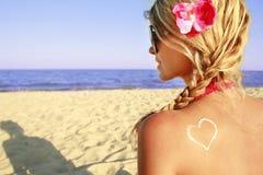 Καρδιά της κρέμας στο θηλυκό πίσω στην παραλία Στοκ Εικόνες