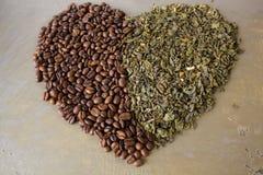 Καρδιά του μαύρου καφέ σιταριών και των πράσινων φύλλων τσαγιού στοκ εικόνες
