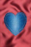 Καρδιά του υφάσματος τζιν με το κίτρινο ράψιμο στο κόκκινο μετάξι Στοκ φωτογραφία με δικαίωμα ελεύθερης χρήσης