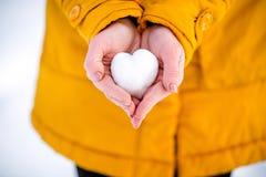 Καρδιά του χιονιού στα χέρια ενός κοριτσιού Στοκ Φωτογραφίες