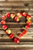 Καρδιά των μήλων στο καφετί ξύλινο υπόβαθρο Στοκ Εικόνα