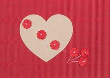 Καρδιά χαρτονιού με τα λουλούδια εγγράφου στο κόκκινο υπόβαθρο Στοκ Φωτογραφία