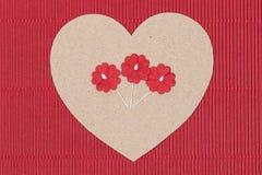 Καρδιά χαρτονιού με τα λουλούδια εγγράφου στο κόκκινο υπόβαθρο. Στοκ Εικόνες