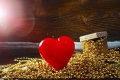 Καρδιά, δώρο και φλόγες στο ξύλινο υπόβαθρο Στοκ Εικόνες