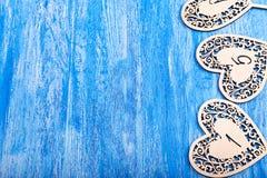 Καρδιά Ooden που χαράζεται σε ένα μπλε ξύλινο υπόβαθρο Στοκ φωτογραφίες με δικαίωμα ελεύθερης χρήσης