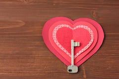 Καρδιές και κλειδί σε ξύλινο Στοκ Φωτογραφία