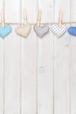 Καρδιές παιχνιδιών ημέρας βαλεντίνων που κρεμούν στο σχοινί πέρα από την άσπρη ξύλινη πλάτη Στοκ Εικόνες