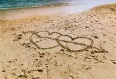 Καρδιές στην άμμο κοντά στον ωκεανό Στοκ Φωτογραφίες