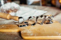 Κασσίτεροι ψησίματος σε έναν ξύλινο πίνακα που καλύπτεται με το ψημένο αλεύρι Κυλημένη ζύμη με ένα σχέδιο και ένα μπισκότο των δι στοκ εικόνα