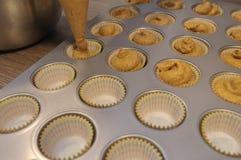Κασσίτερος πλήρωσης Baker με muffin κολοκύθας το κτύπημα στοκ εικόνες