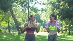 Κατάλληλες γυναίκες με τις πετσέτες που περπατούν στο πάρκο μετά από το workout απόθεμα βίντεο