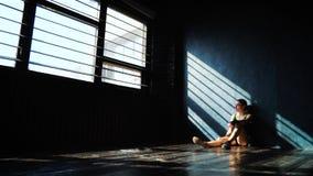 Κατάλληλη άσπρη θηλυκή συνεδρίαση μπόξερ στο πάτωμα κοντά στον τοίχο που στηρίζεται μετά από την κατάρτιση εγκιβωτισμού στη γυμνα απόθεμα βίντεο