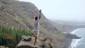 Κατάλληλη γιόγκα χαιρετισμού ήλιων πρακτικών νεαρών άνδρων στο βουνό για τον ωκεανό Νεαρός άνδρας που απολαμβάνει την περισυλλογή απόθεμα βίντεο