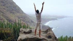 Κατάλληλη γιόγκα χαιρετισμού ήλιων πρακτικών νεαρών άνδρων στο βουνό για τον ωκεανό Νεαρός άνδρας που απολαμβάνει την περισυλλογή φιλμ μικρού μήκους
