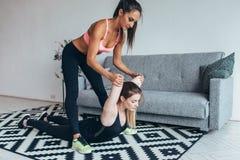 Κατάλληλη γυναίκα που βοηθά το φίλο στην πλάτη που τεντώνει workout στο σπίτι Στοκ Φωτογραφίες