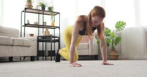Κατάλληλη γυναίκα που κάνει την άσκηση σανίδων στο σπίτι απόθεμα βίντεο