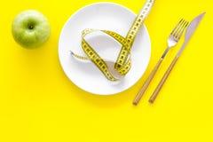 Κατάλληλη διατροφή με την τροφική ίνα για την απώλεια βάρους Apple στο πιάτο που μετρά πλησίον την ταινία στην κίτρινη τοπ άποψη  Στοκ εικόνες με δικαίωμα ελεύθερης χρήσης