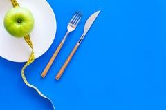 Κατάλληλη διατροφή με την τροφική ίνα για την απώλεια βάρους Apple στο πιάτο που μετρά πλησίον την ταινία στο μπλε αντίγραφο άποψ Στοκ φωτογραφία με δικαίωμα ελεύθερης χρήσης