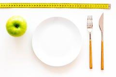 Κατάλληλη διατροφή με την τροφική ίνα για την απώλεια βάρους Apple στο πιάτο που μετρά πλησίον την ταινία στην άσπρη τοπ άποψη υπ Στοκ Εικόνες