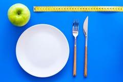 Κατάλληλη διατροφή με την τροφική ίνα για την απώλεια βάρους Apple στο πιάτο που μετρά πλησίον την ταινία στην μπλε τοπ άποψη υπο Στοκ φωτογραφία με δικαίωμα ελεύθερης χρήσης
