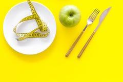 Κατάλληλη διατροφή με την τροφική ίνα για την απώλεια βάρους Apple στο πιάτο που μετρά πλησίον την ταινία στην κίτρινη τοπ άποψη  Στοκ Εικόνες