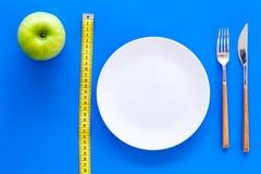 Κατάλληλη διατροφή με την τροφική ίνα για την απώλεια βάρους Apple στο πιάτο που μετρά πλησίον την ταινία στην μπλε τοπ άποψη υπο Στοκ Εικόνες