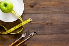 Κατάλληλη διατροφή με την τροφική ίνα για την απώλεια βάρους Apple στο πιάτο που μετρά πλησίον την ταινία στη σκοτεινή ξύλινη κορ Στοκ Εικόνα