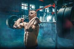 Κατάλληλη επίλυση ανύψωσης νεαρών άνδρων barbells σε μια γυμναστική στοκ εικόνες