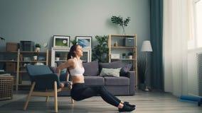 Κατάλληλη νέα γυναίκα που κάνει pushup τις εμβυθίσεις που κρατούν την πολυθρόνα επιλύοντας στο διαμέρισμα απόθεμα βίντεο