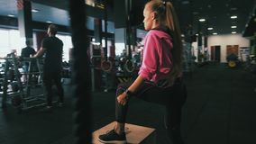 Κατάλληλη νέα γυναίκα που πηδά στη ρόδα σε μια γυμναστική ύφους crossfit Ο θηλυκός αθλητής εκτελεί τα άλματα φιλμ μικρού μήκους