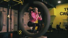 Κατάλληλη νέα γυναίκα που πηδά στη ρόδα σε μια γυμναστική ύφους crossfit Ο θηλυκός αθλητής εκτελεί τα άλματα απόθεμα βίντεο