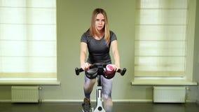 Κατάλληλη νέα γυναίκα που χρησιμοποιεί το ποδήλατο στη γυμναστική Ισχυρός θηλυκός αθλητής που κάνει το καρδιο workout στον κύκλο  απόθεμα βίντεο