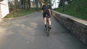 Κατάλληλος αθλητικός ποδηλάτης που τρέχει γρήγορα ανηφορικά Ακολουθήστε τον πυροβολισμό Ισχυροί μυ'ες ποδιών που γυρίζουν τα πεντ απόθεμα βίντεο