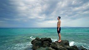 Κατάλληλος αρσενικός αθλητής ικανότητας που στέκεται στους βράχους θάλασσας Στοκ Εικόνες