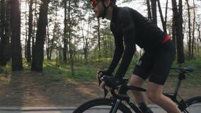 Κατάλληλος βέβαιος ποδηλάτης σε ένα ποδήλατο από τη σέλα στο πάρκο Ισχυροί μυ'ες ποδιών που περιστρέφουν τα πεντάλια Έννοια ανακύ απόθεμα βίντεο