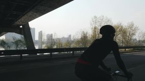 Κατάλληλος και ισχυρός ποδηλάτης που ένα ποδήλατο με την πόλη, τη γέφυρα και τον ποταμό στο υπόβαθρο Έννοια ανακύκλωσης και κατάρ απόθεμα βίντεο