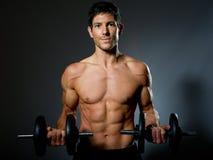 Κατάλληλο νέο αρσενικό με το μεγάλο υγιές σώμα και dumbells Στοκ Φωτογραφίες