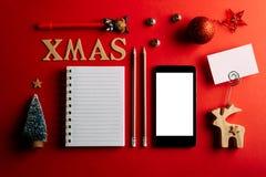Κατάλογος αγορών Χριστουγέννων και κινητό τηλέφωνο, διακοπές που προγραμματίζουν το κόκκινο υπόβαθρο, σημειωματάριο και διακόσμησ στοκ φωτογραφία
