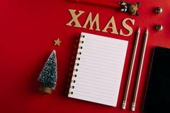 Κατάλογος αγορών Χριστουγέννων και κινητό τηλέφωνο, διακοπές που προγραμματίζουν το κόκκινο υπόβαθρο, σημειωματάριο και διακόσμησ στοκ φωτογραφίες