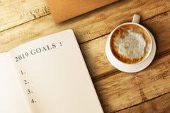 Κατάλογος για 2019 στόχους στο βιβλίο με τον καφέ στον ξύλινο πίνακα στοκ εικόνες