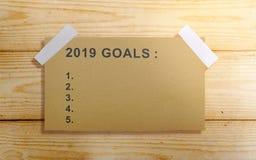 Κατάλογος 2019 στόχων στο καφετί έγγραφο για τον ξύλινο τοίχο στοκ εικόνες
