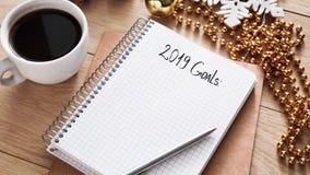 κατάλογος 2019 στόχων στο σημειωματάριο, φλιτζάνι του καφέ στο ξύλινο γραφείο στοκ εικόνα με δικαίωμα ελεύθερης χρήσης