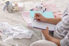 Κατάλογος συσκευασίας γραψίματος εγκύων γυναικών για το νοσοκομείο μητρότητας στο κρεβάτι στο σπίτι στοκ εικόνες