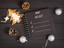 κατάλογος του 2018 στόχων με ένα σημειωματάριο, τους κώνους και τις διακοσμήσεις Χριστουγέννων σε έναν ξύλινο πίνακα Στοκ φωτογραφίες με δικαίωμα ελεύθερης χρήσης