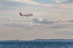 Κατάνια, Σικελία Ιταλία - 01 13 2019: Ένα κόκκινο και άσπρο αεροπλάνο με τα πλαίσια προσγειώνεται πέρα από τη Μεσόγειο στον αερολ στοκ εικόνες